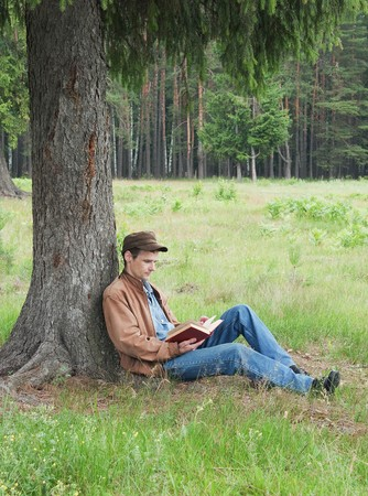 under a tree: Person reads book, sitting in wood under a tree Stock Photo