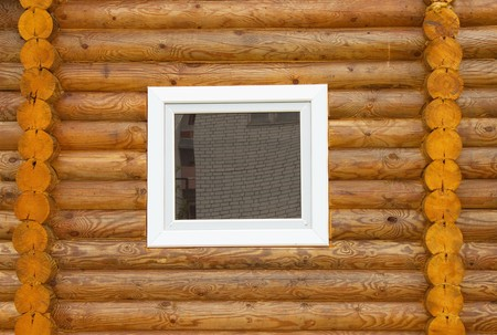 Plastic window is inserted into a wooden wall Stock Photo