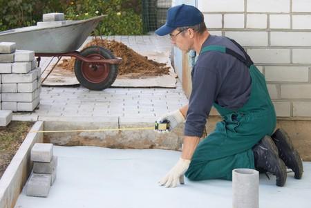 road paving: El trabajador prepara un lugar para un pavimento