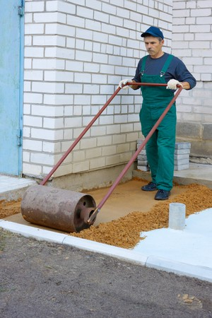 The worker prepares a place for a paving