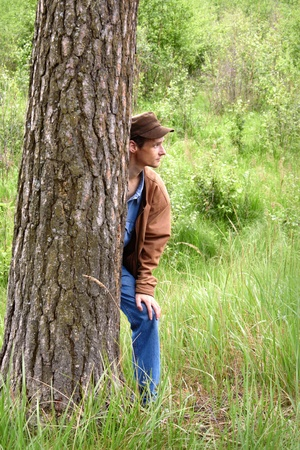 Young man hiding behind a tree