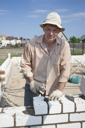 �aucasian: Bricklayer builds a wall of white brick