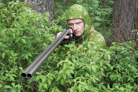 Angry  hunter with an old gun in the bushes