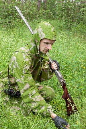 old rifle: Hunter with an old rifle is considering the trail in a grass
