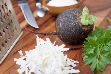 Schwarzer Rettich reiben auf einer kleinen Reibe f�r Salat Vorbereitung Lizenzfreie Bilder