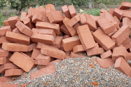 sameness: Lots red clay bricks lying on the gravel