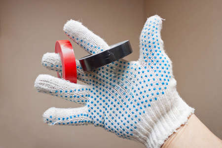 handbreadth: Hand in a glove and an insulating tape Stock Photo