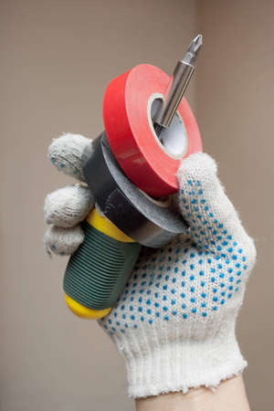 handbreadth: Screwdriver and electrical tape in his hand Stock Photo
