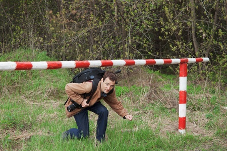 perpetrator: A young man with a backpack passes under the barrier Stock Photo
