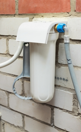 Housing water filter is mounted on a brick wall