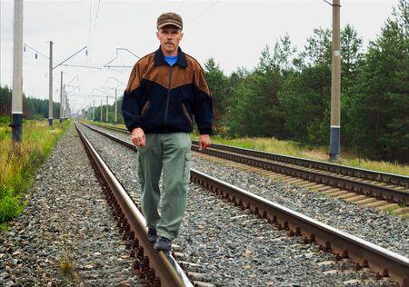 intolerable: An elderly man walking on railway track Stock Photo