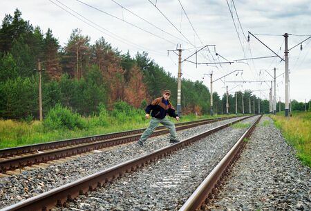 intolerable: An elderly man risky crosses a railway embankment
