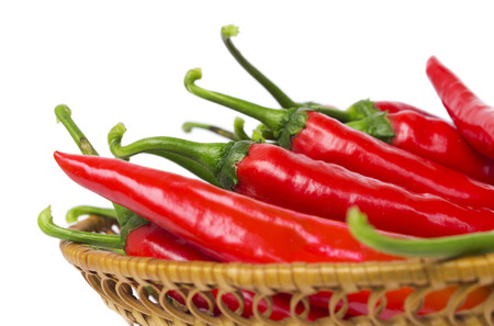 Lot of hot pepper in a straw dish photo