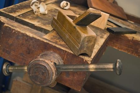 vise: Tornillo de banco de madera vieja y herramientas en un taller