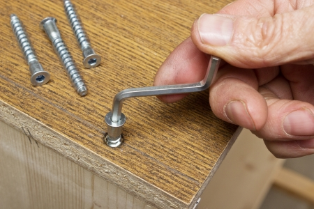 tightening: Tightening the metal screws by hand when assembling furniture