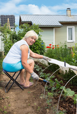 Elderly woman is engaged in weeding in the garden, sitting on a chair photo
