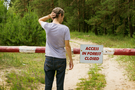 idea hurdle: A man stands in front of a barrier in the forest in inflammable period