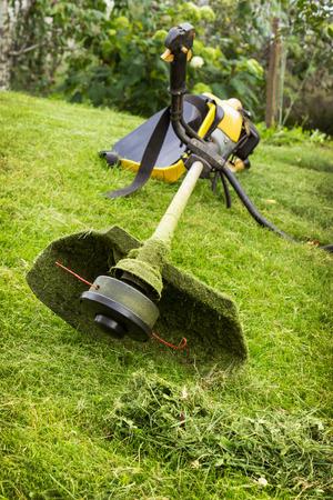 Benzin Trimmer auf der geneigten Rasen im Garten