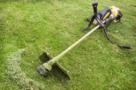 Benzin-Trimmer auf der geneigten Rasen im Garten