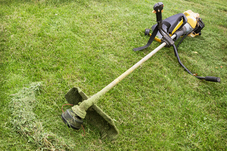 Petrol trimmer is on the sloped lawn in the garden