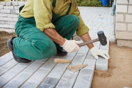 materiales para construccion: Asistente pone los bloques, por lo que la acera Foto de archivo