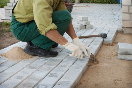 Worker puts the blocks, creating a sidewalk photo