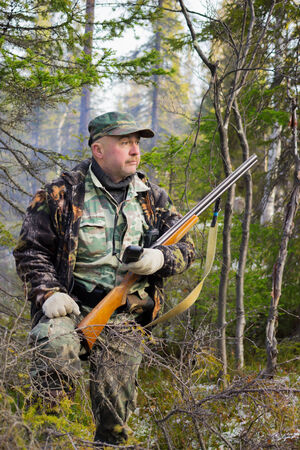 defines: Hunter defines the location with the help of the navigator, taiga, Russia Stock Photo