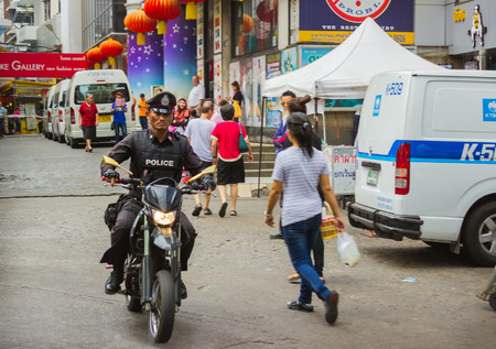 THAILAND, BANGKOK - FEB 20: Policeman riding a motorbike  in the Thai capital February 20, 2015 in Bangkok, Thailand. For convenience patrols in the city, the police used scooters
