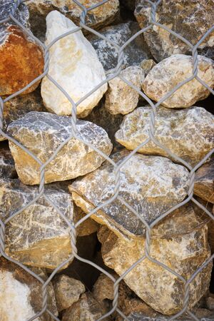 walling: Background of large stones and metallic grid