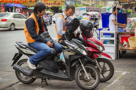 congested: BANGKOK, THAILAND - FEB 20, 2015: Taxi drivers on scooters waiting for customers in Bangkok. Motorbike taxis are a popular choice for the Thai  heavily congested roads