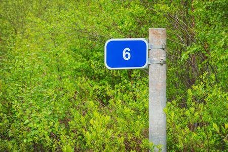 milepost: Milepost mileage kilometrs on the roadside  in the bushes