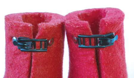 clasps: Iron clasps on the felt red boots on white background