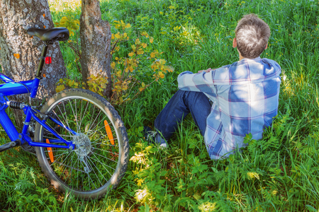 aloneness: lonely man is resting on a hill in the shade of a tree Stock Photo