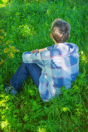 aloneness: Young man is resting in the shade and looking into the distance Stock Photo