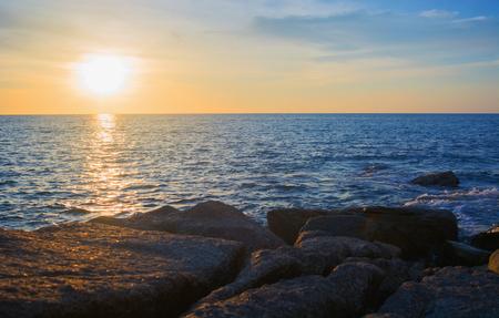 Rocky seashore and sunset over the sea Фото со стока