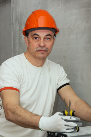 Portrait of an electrician in a protective helmet and with a tool in hand Archivio Fotografico