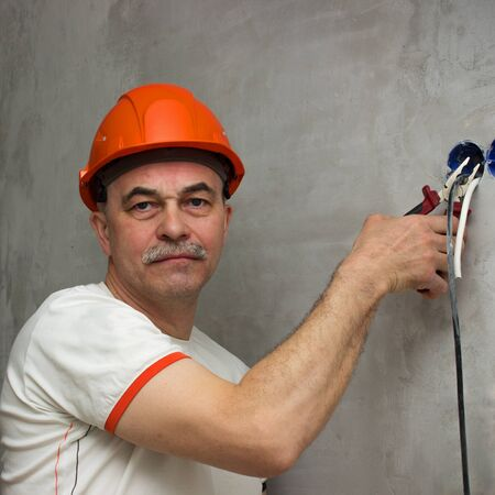 Strange man with a stern face cuts the wiring. Produces deversion 写真素材