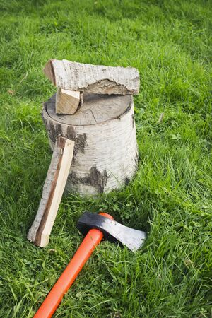 Splitting axe lying on the grass and nearby birch firewood. Preparation for winter Stok Fotoğraf