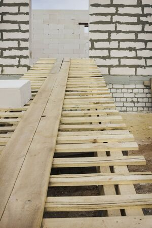 Enter a wooden gangway into a residential building under construction