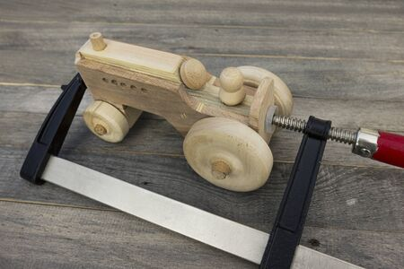 Gluing process. Handmade wooden toy on the old table