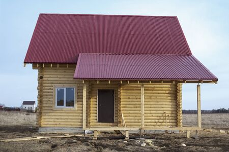 Wooden small house with iron red roof and canopy Standard-Bild