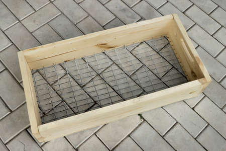 Sieve in a wooden frame for sifting soil lies on a stone floor