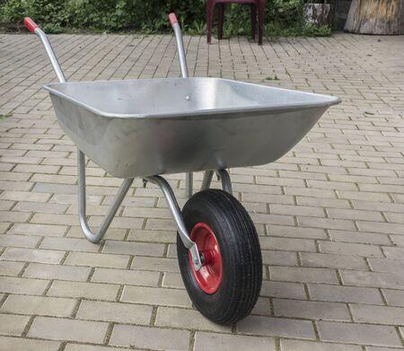 Wheelbarrow on stone floor. Garden metal cart with pneumatic wheel