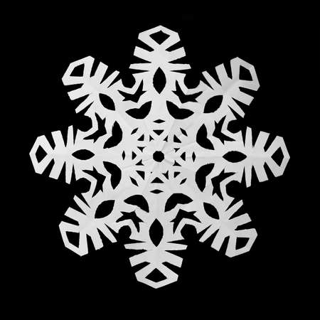 White snowflake cut out of paper lies on a black background  イラスト・ベクター素材