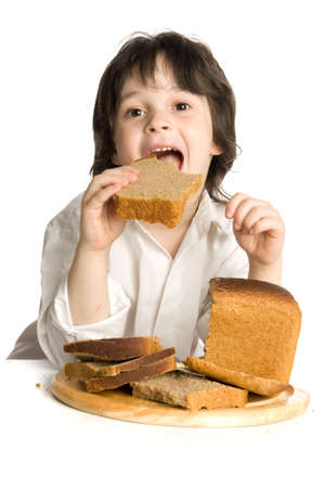 bread loaf: The little boy which eating a  bread on desk Stock Photo