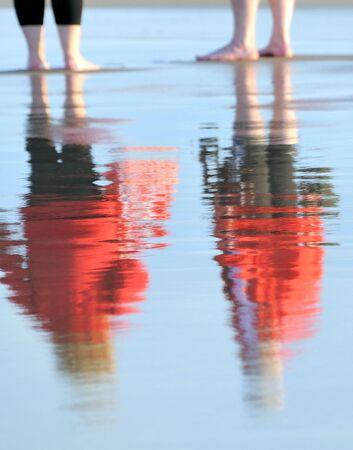 reflexion: Reflexi�n de figuras de dos personas en la arena mojada. Costa del mar B�ltico. Por la noche  Foto de archivo