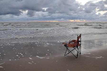 broken chair: Broken red fisherman chair on a beach sand. Storm by the Baltic sea