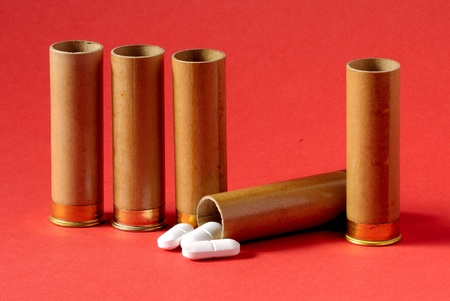 uncontrolled: Carefully - medicines. The uncontrolled use of medicines is life-threatening. Tablets fill a gun sleeve. Stock Photo