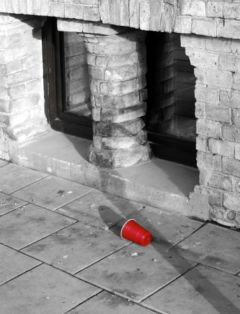 oldtown: Red plastic cup on old-town city sidewalk Stock Photo