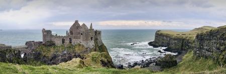 castillo medieval: Un panorama con los detalles del famoso castillo de Dunluce retroiluminada - un punto de referencia desde el condado de Antrim, Irlanda del Norte